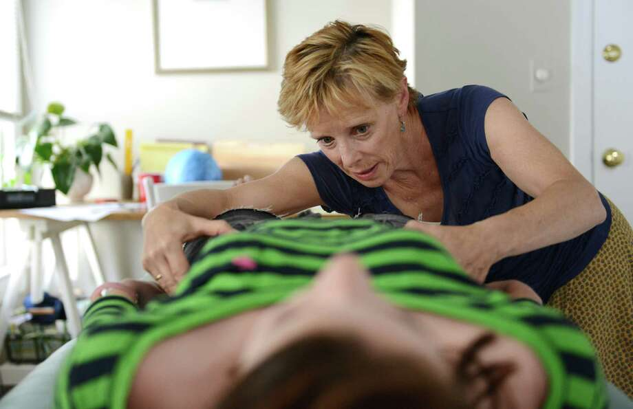Janet Schroeder treats patient Emma Beers, 13, of Bethel, at Integrated Pain and Stress Relief in Bethel, Conn. on Wednesday, June 5, 2013.  Beers had symptoms of headaches, nausea and dizziness from a concussion and said she's seen a drop in pain since being treated by Schroeder. Photo: Tyler Sizemore / The News-Times
