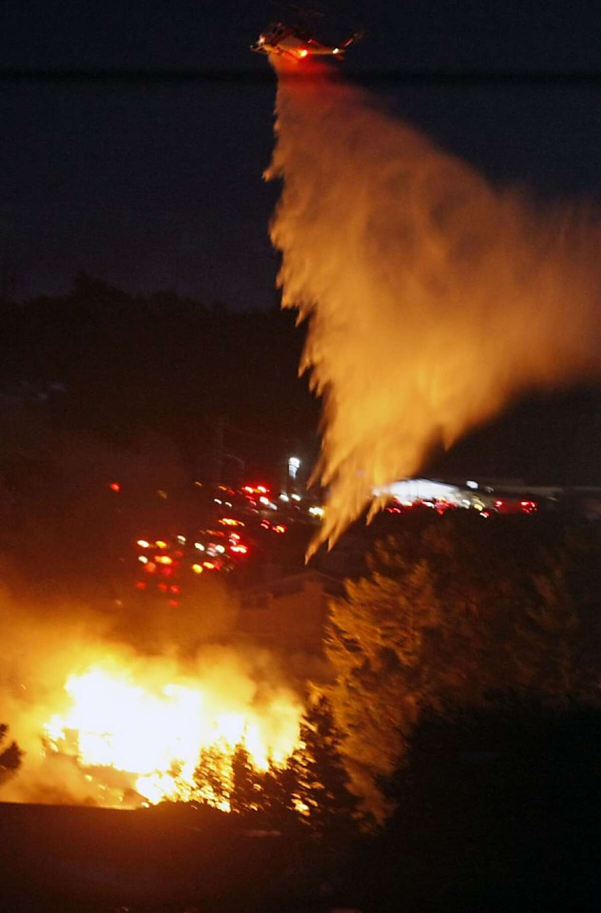 A helicopter works to contain a fast moving fire caused by an explosion in a San Bruno nighborhood Thursday, Sept. 9, 2010.