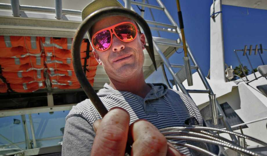 On Tuesday, June 4, 2013, Jason Johnston of Mesquite, Texas, holds the large hook he used the 12-foot, 1,300-plus-pound shortfin mako shark he caught the day before off the coast of Huntington Beach, California. (Don Bartletti/Los Angeles Times/MCT) Photo: Don Bartletti, MBR / Los Angeles Times