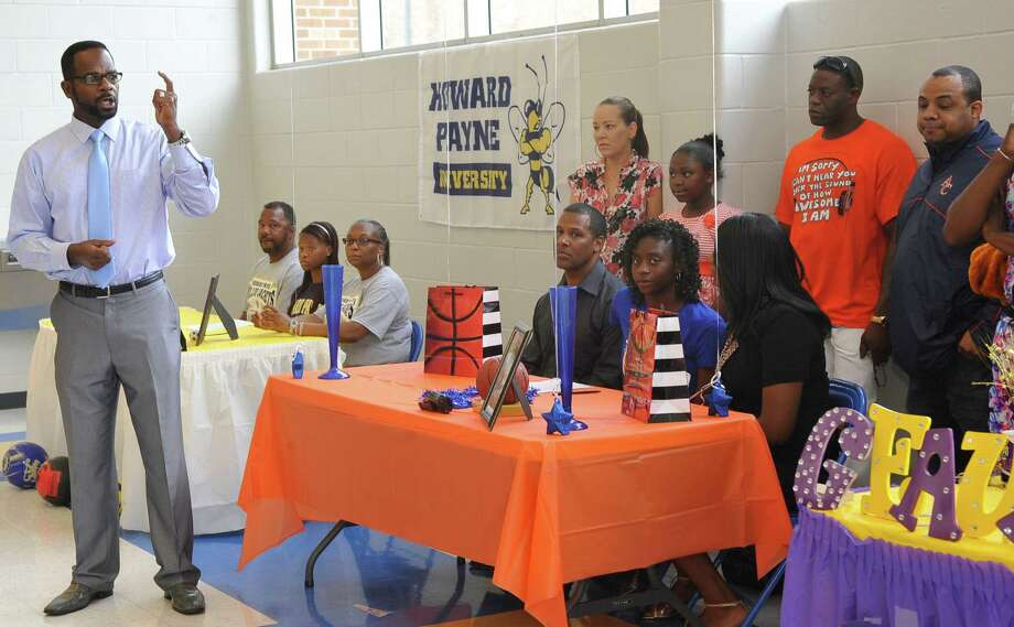FILE - Ozen Principal Odis Norris, left, talks to the four athletes and the audience about not forgetting their education. Four Ozen High School athletes signed Wednesday morning to play college athletics in the fall. Bealoved Brown signed with LSU to run track, Jakobi Jones signed with South Plains College to run track, SanQueisha Rawls signed with Angelina College to play basketball and Paige Marks signed with Howard Payne College to play soccer. Dave Ryan/The Enterprise Photo: Dave Ryan