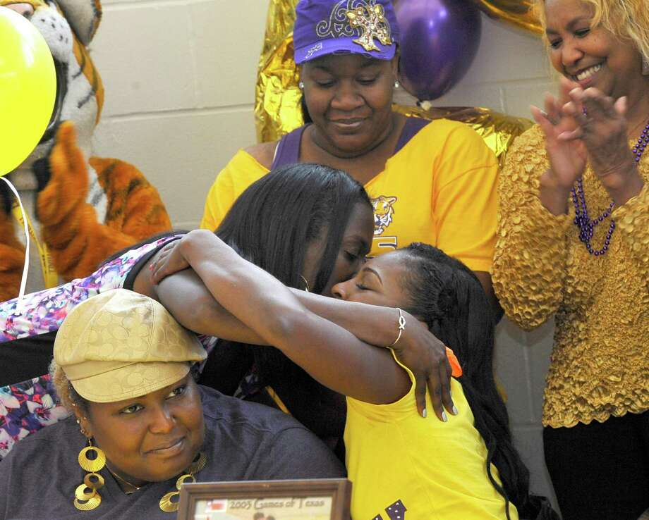 Ozen coach Tammy-Walker Brown, left, kisses and hergs her daughter Bealoved Brown. Four Ozen High School athletes signed Wednesday morning to play college athletics in the fall. Bealoved Brown signed with LSU to run track, Jakobi Jones signed with South Plains College to run track, SanQueisha Rawls signed with Angelina College to play basketball and Paige Marks signed with Howard Payne College to play soccer. Dave Ryan/The Enterprise Photo: Dave Ryan