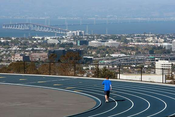 A jogger takes advantage of San Mateo City College track and its almost perfect weather and view of the city as he runs laps.