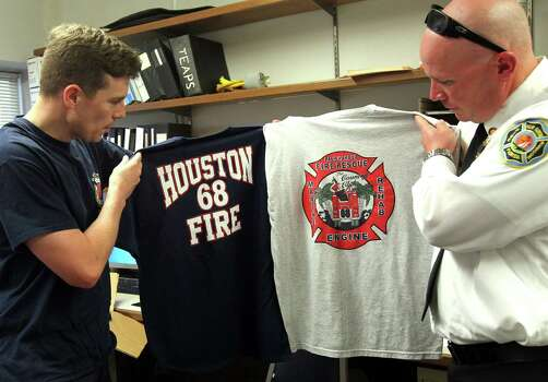 Houston firefighter Glen Mears, right, swaps shirts with Florida firefighter C. Eisenhardt at Station 68, where Florida and Dallas comrades filled in on Wednesday. Photo: Mayra Beltran, Staff / © 2013 Houston Chronicle