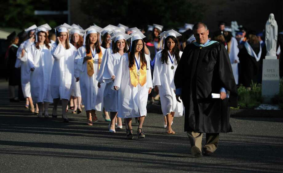 Immaculate High School students walk to the commencement ceremony at St. Mary's Church in Bethel, Conn. on Wednesday, June 5, 2013.  The school graduated 69 students. Photo: Tyler Sizemore / The News-Times