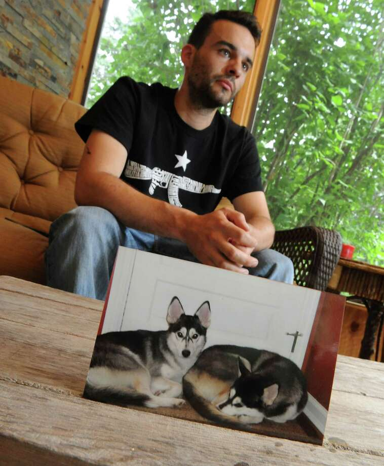 James Terry talks about his recently deceased dog Lois, at left in photo, at his home on Wednesday, June 5, 2013 in Guilderland, N.Y. Terry's Siberian Husky Lois was killed after a state trooper tied the dog to a bumper during a traffic stop and then later drove away with the dog attached. His other dog, Liz, on right, was tied too but was unhurt. (Lori Van Buren / Times Union) Photo: Lori Van Buren / 00022719A