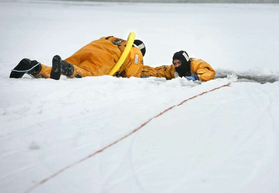 Bridgeport firefighters Christian Teague, left, and Jim Bonosconi participate in ice rescue drills on Lake Forest in Bridgeport, Conn on Wednesday, January 13, 2010. Photo: Brian A. Pounds / Connecticut Post