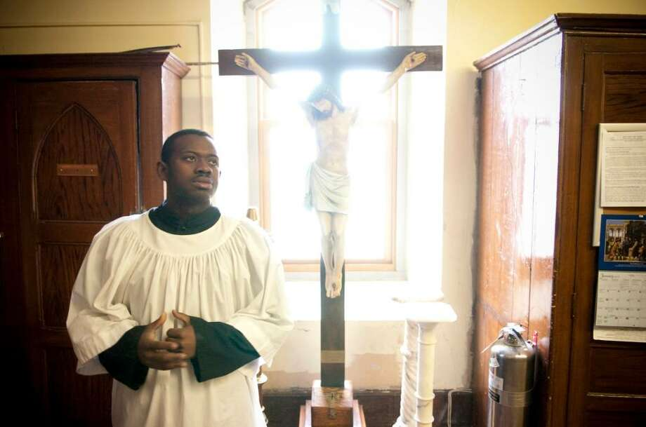 Altar server Ferry Galbert, a native of Haiti, prepares for a mass at St. John's Church in Stamford, Conn. dedicated the victims and survivors of yesterday's deadly earthquake in Haiti. Galbert has been able to reach some of his family members by phone but many others, including his grandmother have been unreacheable and their conditions are unknown. Photo: Chris Preovolos / Stamford Advocate