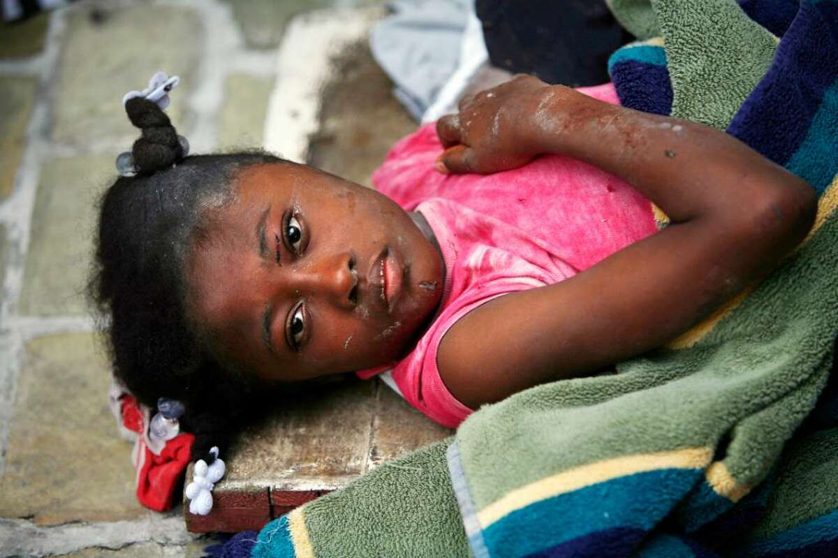 An injured girl lies on the side of the road as she is attended to the day after an earthquakeÜhit Port-au-Prince, Haiti, Wednesday, Jan. 13, 2010. A 7.0-magnitude earthquake hit Haiti on Tuesday. (AP Photo/Ricardo Arduengo)
