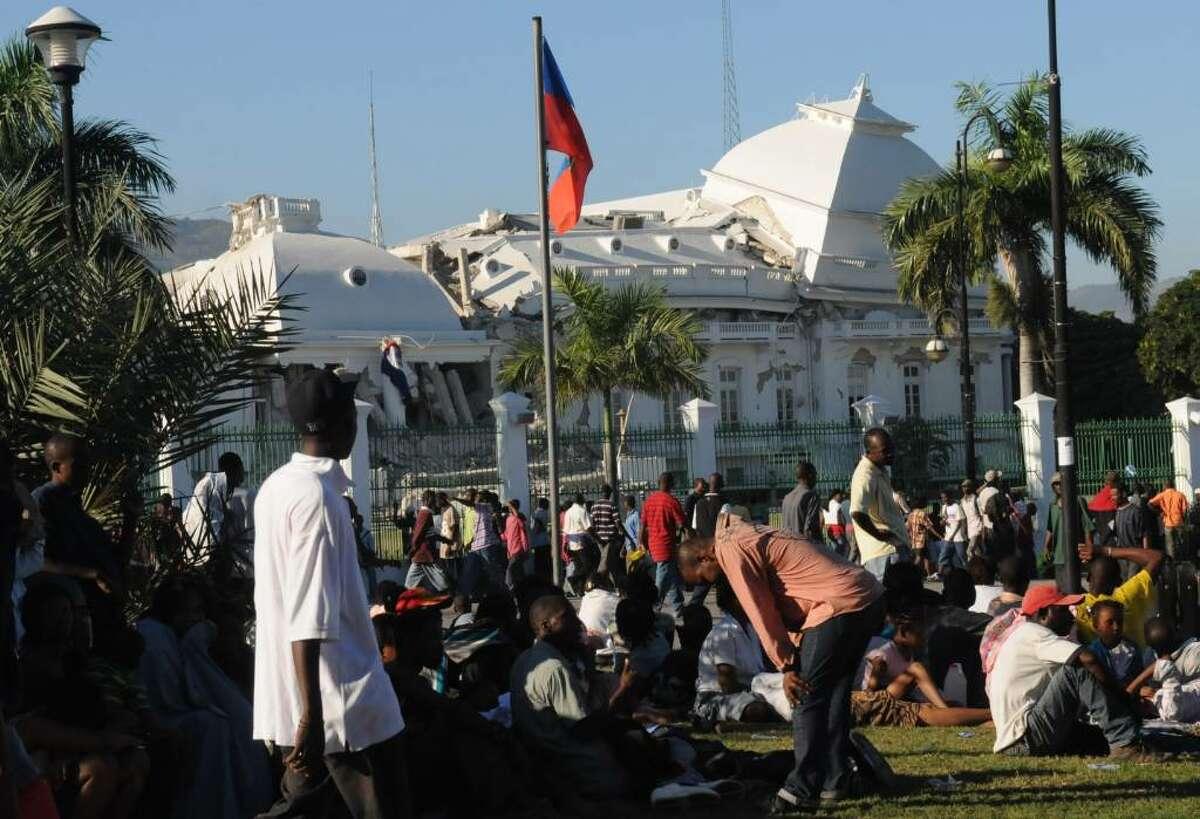 People gather outside Haiti's National Palace which was damaged by an earthquake in Port-au-Prince, Haiti, Wednesday, Jan. 13, 2010. A 7.0-magnitude earthquake hit Haiti on Tuesday. (AP Photo/Jorge Cruz)