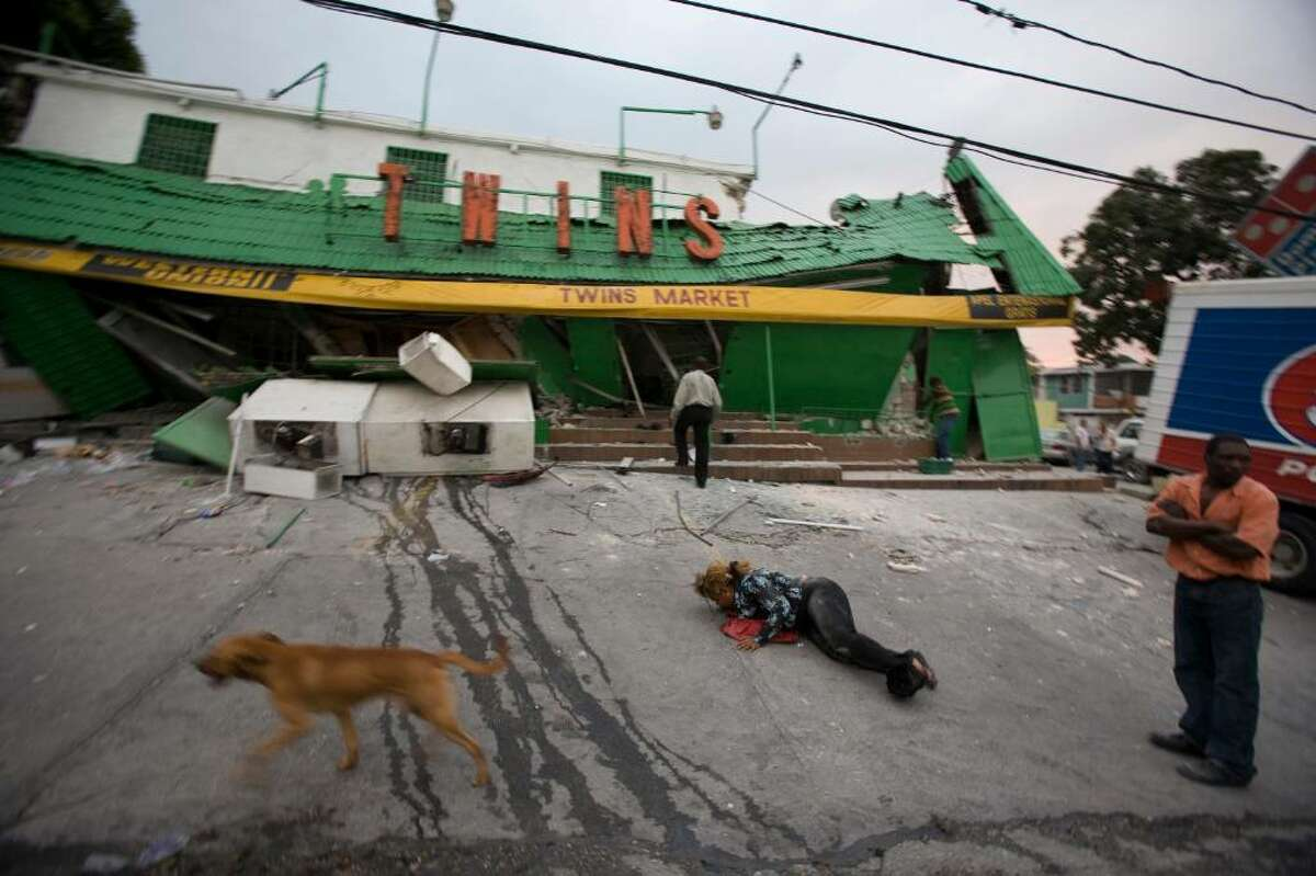 A woman lies on the ground as others stand outside a market that collapsed after a powerful earthquake struck Port-au-Prince, Haiti, Tuesday Jan. 12, 2010. (AP Photo/Cris Bierrenbach)