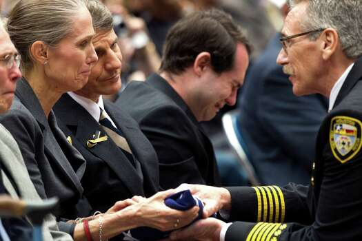 Mary Sullivan, left, mother of firefighter Anne Sullivan, is presented a flag by Houston Fire Chief Terry Garrison during a memorial service honoring Houston firefighters Robert Bebee, Robert Garner, Matthew Renaud, and Anne Sullivan at Reliant Stadium Wednesday, June 5, 2013, in Houston. The four firefighters died in a 5-alarm fire while searching for people they thought might be trapped inside a burning motel and restaurant last Friday. Photo: Brett Coomer, Houston Chronicle / © 2013  Houston Chronicle