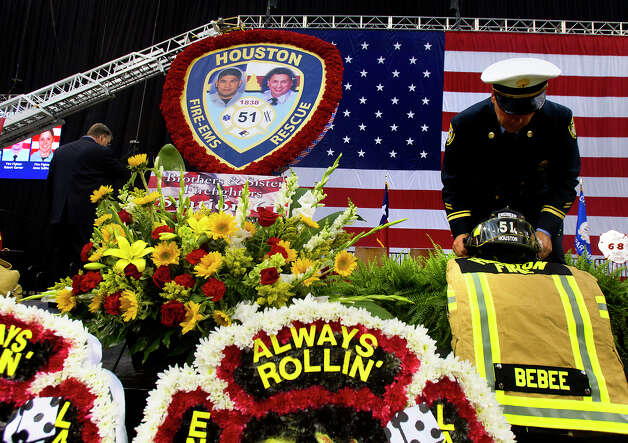 A firefighter prepares the gear of Engineer Bebee before a memorial service honoring four Houston firefighters at Reliant Stadium Wednesday, June 4, 2013. In Houston. Four firefighters died when a part of a building collapsed on them while they were searching for people they thought might be trapped inside a burning motel and restaurant last Friday. Photo: Cody Duty, Houston Chronicle / © 2013 Houston Chronicle
