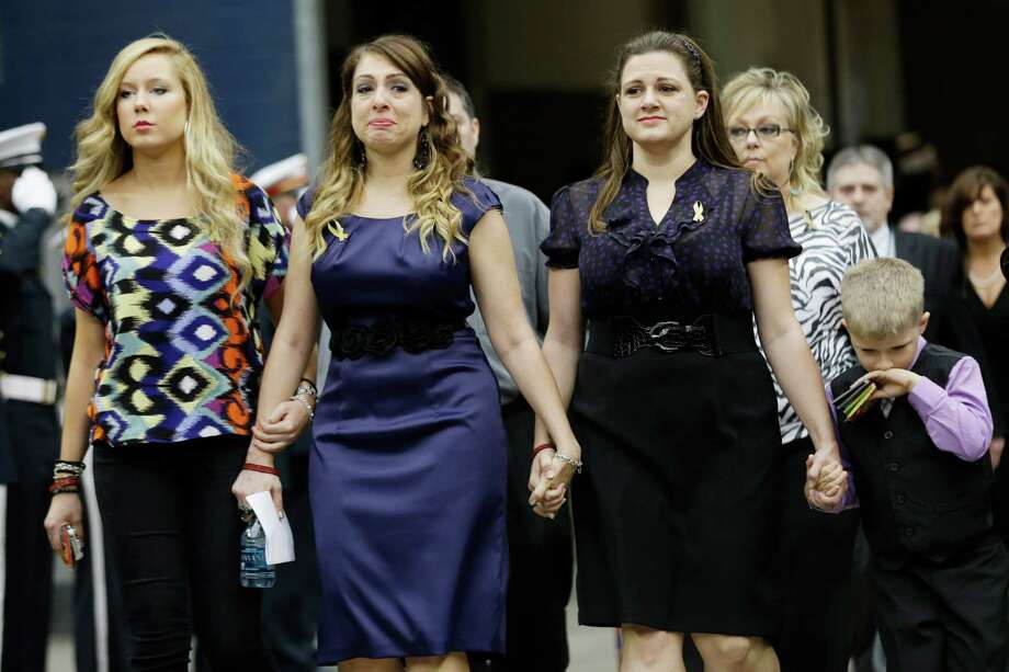 Nicole Garner, center, sister of firefighter Robert Garner, walks into a memorial service honoring Houston firefighters Robert Bebee, Robert Garner, Matthew Renaud, and Anne Sullivan at Reliant Stadium Wednesday, June 5, 2013, in Houston. The four firefighters died in a 5-alarm fire while searching for people they thought might be trapped inside a burning motel and restaurant last Friday. Photo: Brett Coomer, Houston Chronicle / © 2013  Houston Chronicle