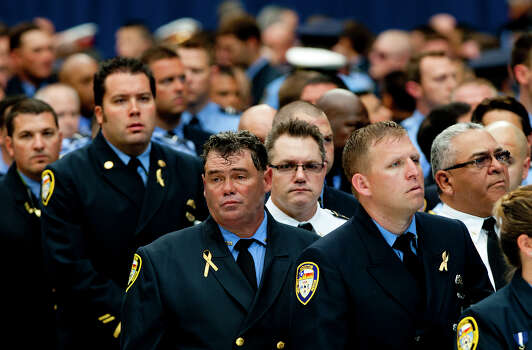 Firefighters enter Reliant Stadium before a memorial service honoring four Houston firefighters, Wednesday, June 5, 2013. In Houston. Four firefighters died when a part of a building collapsed on them while they were searching for people they thought might be trapped inside a burning motel and restaurant last Friday. Photo: Cody Duty, Houston Chronicle / © 2013 Houston Chronicle