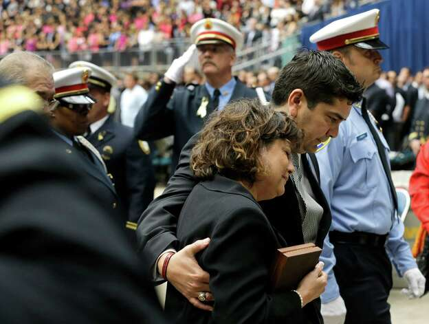 Barbara Perez is escorted by David Renaud from a memorial service honoring Houston firefighters Robert Bebee, Robert Garner, Matthew Renaud, and Anne Sullivan at Reliant Stadium Wednesday, June 5, 2013, in Houston. The four firefighters died in a 5-alarm fire while searching for people they thought might be trapped inside a burning motel and restaurant last Friday. Photo: Brett Coomer, Houston Chronicle / © 2013  Houston Chronicle