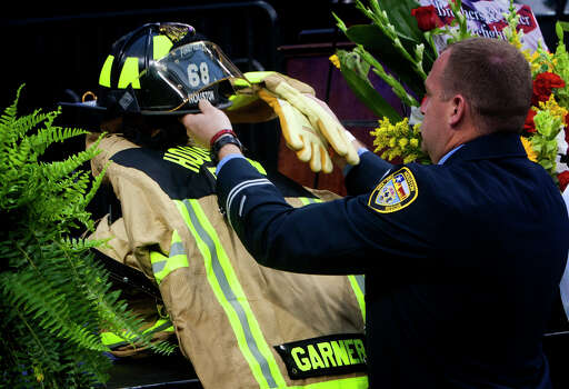 A firefighter places a helmet on the gear of Firefighter Garner before a memorial service honoring four Houston firefighters at Reliant Stadium Wednesday, June 5, 2013. In Houston. Four firefighters died when a part of a building collapsed on them while they were searching for people they thought might be trapped inside a burning motel and restaurant last Friday. Photo: Cody Duty, Houston Chronicle / © 2013 Houston Chronicle