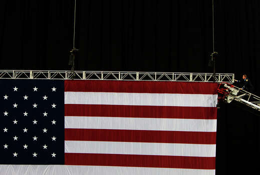 A firefighter adjusts an American flag before a memorial service honoring four Houston firefighters at Reliant Stadium Wednesday, June 5, 2013. In Houston. Four firefighters died when a part of a building collapsed on them while they were searching for people they thought might be trapped inside a burning motel and restaurant last Friday. Photo: Cody Duty, Houston Chronicle / © 2013 Houston Chronicle