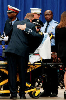A firefighter receives a hug after he was injured in a fire before a memorial service honoring the four Houston firefighters that perished in a fire, at Reliant Stadium Wednesday, June 5, 2013. In Houston. Four firefighters died when a part of a building collapsed on them while they were searching for people they thought might be trapped inside a burning motel and restaurant last Friday. Photo: Cody Duty, Houston Chronicle / © 2013 Houston Chronicle