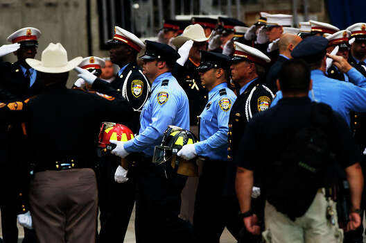Firefighters carry the helmets of the four fallen firefighters before a memorial service in their honor at Reliant Stadium Wednesday, June 5, 2013. In Houston. Four firefighters died when a part of a building collapsed on them while they were searching for people they thought might be trapped inside a burning motel and restaurant last Friday. Photo: Cody Duty, Houston Chronicle / © 2013 Houston Chronicle