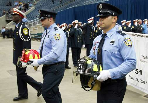 Houston firefighters carry helmets into a memorial service honoring Houston firefighters Robert Bebee, Robert Garner, Matthew Renaud, and Anne Sullivan at Reliant Stadium Wednesday, June 5, 2013, in Houston. The four firefighters died in a 5-alarm fire while searching for people they thought might be trapped inside a burning motel and restaurant last Friday. Photo: Brett Coomer, Houston Chronicle / © 2013  Houston Chronicle