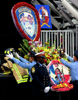A firefighter places a helmet on the gear of a fallen firefighter during a memorial service honoring four Houston firefighters at Reliant Stadium Wednesday, June 5, 2013. In Houston. Four firefighters died when a part of a building collapsed on them while they were searching for people they thought might be trapped inside a burning motel and restaurant last Friday. Photo: Cody Duty, Houston Chronicle / © 2013 Houston Chronicle