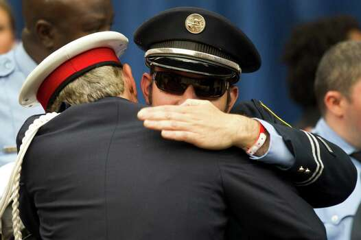 Injured Houston firefighter Anthony Livesay is embraced during a memorial service honoring Houston firefighters Robert Bebee, Robert Garner, Matthew Renaud, and Anne Sullivan at Reliant Stadium Wednesday, June 5, 2013, in Houston. The four firefighters died in a 5-alarm fire while searching for people they thought might be trapped inside a burning motel and restaurant last Friday. Livesay was injured in the same fire the four perished. Photo: Brett Coomer, Houston Chronicle / © 2013  Houston Chronicle