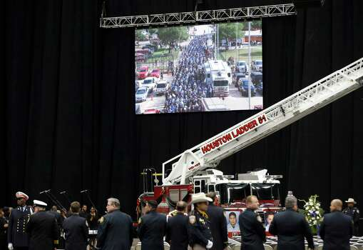 A long line of firefighter procession is shown on a video screen before a memorial service honoring Houston firefighters Robert Bebee, Robert Garner, Matthew Renaud, and Anne Sullivan at Reliant Stadium Wednesday, June 5, 2013, in Houston. The four firefighters died in a 5-alarm fire while searching for people they thought might be trapped inside a burning motel and restaurant last Friday. Photo: Brett Coomer, Houston Chronicle / © 2013  Houston Chronicle