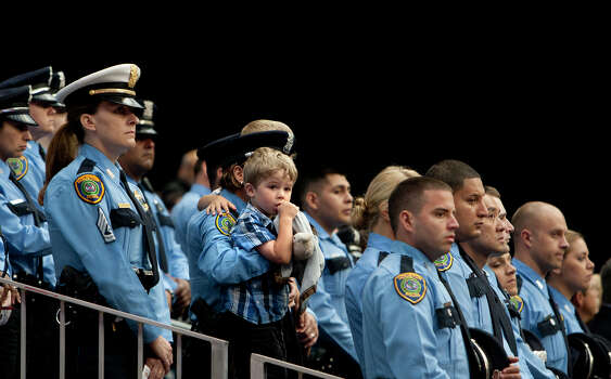 Houston Police stand during a memorial service honoring four Houston firefighters at Reliant Stadium Wednesday, June 5, 2013. In Houston. Four firefighters died when a part of a building collapsed on them while they were searching for people they thought might be trapped inside a burning motel and restaurant last Friday. Photo: Cody Duty, Houston Chronicle / © 2013 Houston Chronicle