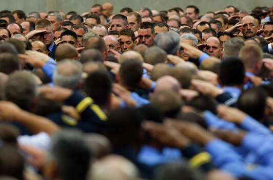 Firefighters salute during a memorial service honoring four Houston firefighters at Reliant Stadium Wednesday, June 5, 2013. In Houston. Four firefighters died when a part of a building collapsed on them while they were searching for people they thought might be trapped inside a burning motel and restaurant last Friday. Photo: Cody Duty, Houston Chronicle / © 2013 Houston Chronicle