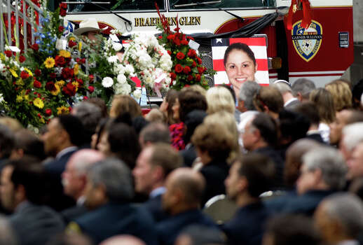 A photo of firefighter Anne Sullivan overlooks the crowd during a memorial service honoring four Houston firefighters, Wednesday, June 5, 2013. In Houston. Four firefighters died when a part of a building collapsed on them while they were searching for people they thought might be trapped inside a burning motel and restaurant last Friday. Photo: Cody Duty, Houston Chronicle / © 2013 Houston Chronicle