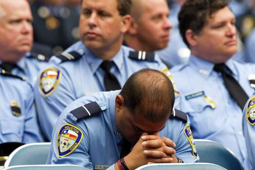 A Houston firefighter bows his head during a memorial service honoring Houston firefighters Robert Bebee, Robert Garner, Matthew Renaud, and Anne Sullivan at Reliant Stadium Wednesday, June 5, 2013, in Houston. The four firefighters died in a 5-alarm fire while searching for people they thought might be trapped inside a burning motel and restaurant last Friday. Photo: Brett Coomer, Houston Chronicle / © 2013  Houston Chronicle