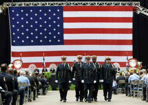 The Houston Fire Department Honor Guard marches away from the stage during a memorial service honoring Houston firefighters Robert Bebee, Robert Garner, Matthew Renaud, and Anne Sullivan at Reliant Stadium Wednesday, June 5, 2013, in Houston. The four firefighters died in a 5-alarm fire while searching for people they thought might be trapped inside a burning motel and restaurant last Friday. Photo: Brett Coomer, Houston Chronicle / © 2013  Houston Chronicle