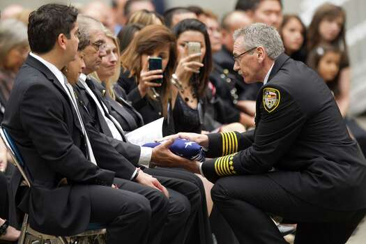 Houston Fire Chief Terry Garrison, right, presents the family of Capt. Matthew Renaud a flag during a memorial service honoring Houston firefighters Robert Bebee, Robert Garner, Matthew Renaud, and Anne Sullivan at Reliant Stadium Wednesday, June 5, 2013, in Houston. The four firefighters died in a 5-alarm fire while searching for people they thought might be trapped inside a burning motel and restaurant last Friday. Photo: Brett Coomer, Houston Chronicle / © 2013  Houston Chronicle