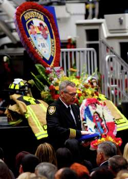 Houston Fire Chief Terry Garrison presents a flag during a memorial service honoring four Houston firefighters at Reliant Stadium Wednesday, June 5, 2013. In Houston. Four firefighters died when a part of a building collapsed on them while they were searching for people they thought might be trapped inside a burning motel and restaurant last Friday. Photo: Cody Duty, Houston Chronicle / © 2013 Houston Chronicle