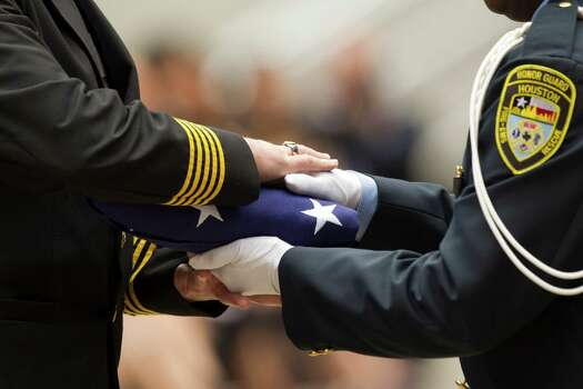 Houston Fire Chief Terry Garrison takes a flag from a n Honor Guard member during a memorial service honoring Houston firefighters Robert Bebee, Robert Garner, Matthew Renaud, and Anne Sullivan at Reliant Stadium Wednesday, June 5, 2013, in Houston. The four firefighters died in a 5-alarm fire while searching for people they thought might be trapped inside a burning motel and restaurant last Friday. Photo: Brett Coomer, Houston Chronicle / © 2013  Houston Chronicle