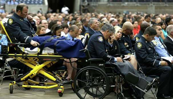 Injured Houston firefighters Anthony Livesay, left, and Robert Yarbrough bow their heads during a memorial service honoring Houston firefighters Robert Bebee, Robert Garner, Matthew Renaud, and Anne Sullivan at Reliant Stadium Wednesday, June 5, 2013, in Houston. The four firefighters died in a 5-alarm fire while searching for people they thought might be trapped inside a burning motel and restaurant last Friday. Photo: Brett Coomer, Houston Chronicle / © 2013  Houston Chronicle