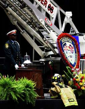 A member of the Houston Fire Department Honor Guard rings a bell in honor of the fallen firefighters during a memorial service in their honor at Reliant Stadium Wednesday, June 5, 2013. In Houston. Four firefighters died when a part of a building collapsed on them while they were searching for people they thought might be trapped inside a burning motel and restaurant last Friday. Photo: Cody Duty, Houston Chronicle / © 2013 Houston Chronicle