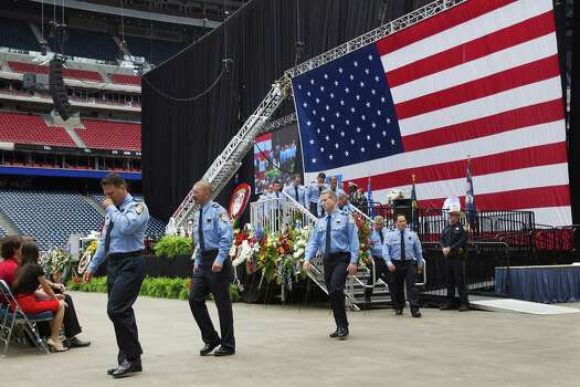 Houston firefighters from stations 51 and 68 walk off the stage after honoring their fallen comrades during a memorial service for Houston firefighters Robert Bebee, Robert Garner, Matthew Renaud, and Anne Sullivan at Reliant Stadium Wednesday, June 5, 2013, in Houston. The four firefighters died in a 5-alarm fire while searching for people they thought might be trapped inside a burning motel and restaurant last Friday. Photo: Brett Coomer, Houston Chronicle / © 2013  Houston Chronicle
