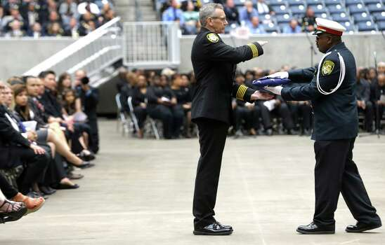 Houston Fire Chief Terry Garrison, left, takes a flag from a member of the HFD Honor Guard during a memorial service honoring Houston firefighters Robert Bebee, Robert Garner, Matthew Renaud, and Anne Sullivan at Reliant Stadium Wednesday, June 5, 2013, in Houston. The four firefighters died in a 5-alarm fire while searching for people they thought might be trapped inside a burning motel and restaurant last Friday. Photo: Brett Coomer, Houston Chronicle / © 2013  Houston Chronicle