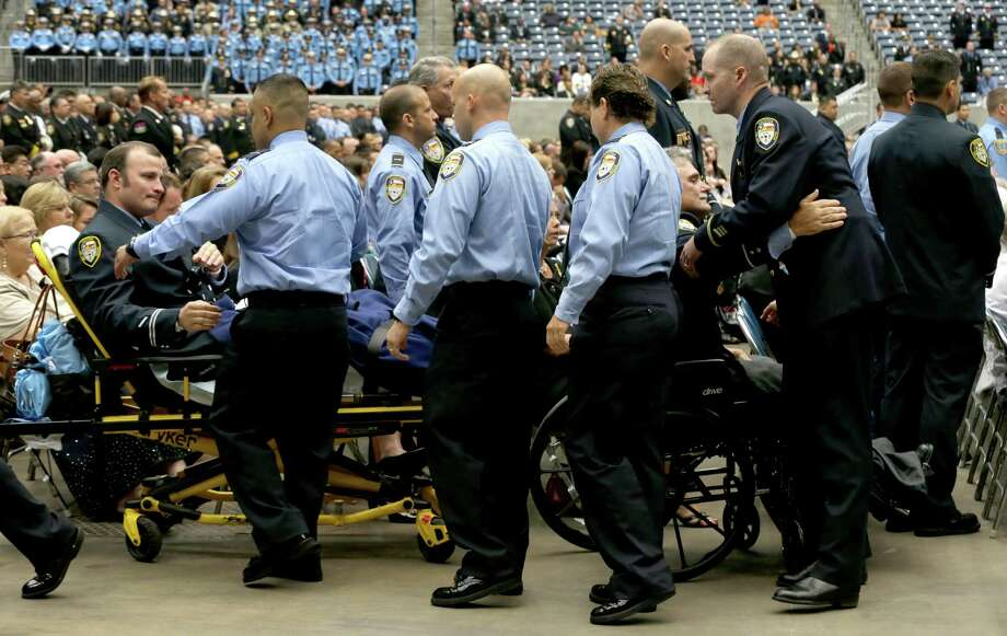 On Wednesday, Houston firefighters greet injured firefighters Anthony Livesay, left, and Robert Yarbrough, lower right, during the memorial service for the four responders killed in last week's fire at the Southwest Inn. Photo: Brett Coomer, Houston Chronicle / © 2013  Houston Chronicle
