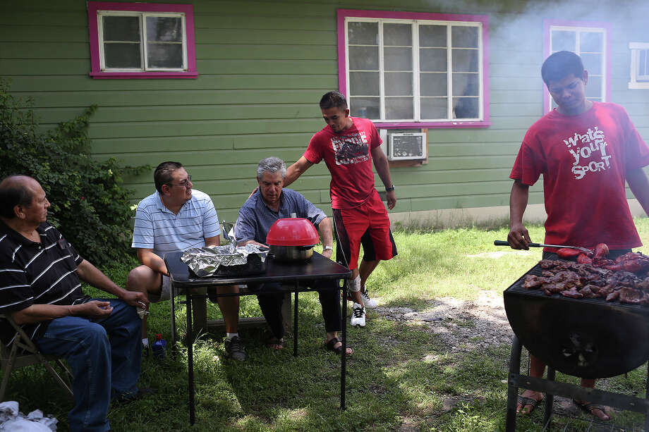 A 23-year-old former resident of Posada Guadalupe, center, asks Father Phillip Ley for a favor while a current resident, right, monitors a grill at Posada Guadalupe in San Antonio on Monday, May 27, 2013. The resident at the grill rode trains for a month to reach the United States from Belize 11 months ago and is working on his GED. From left is Joe Silva, assistant to Father Ley, and Ulises Silva, who is studying to be a priest with Missionary Oblates and is doing service at the home. Photo: Lisa Krantz, San Antonio Express-News / San Antonio Express-News