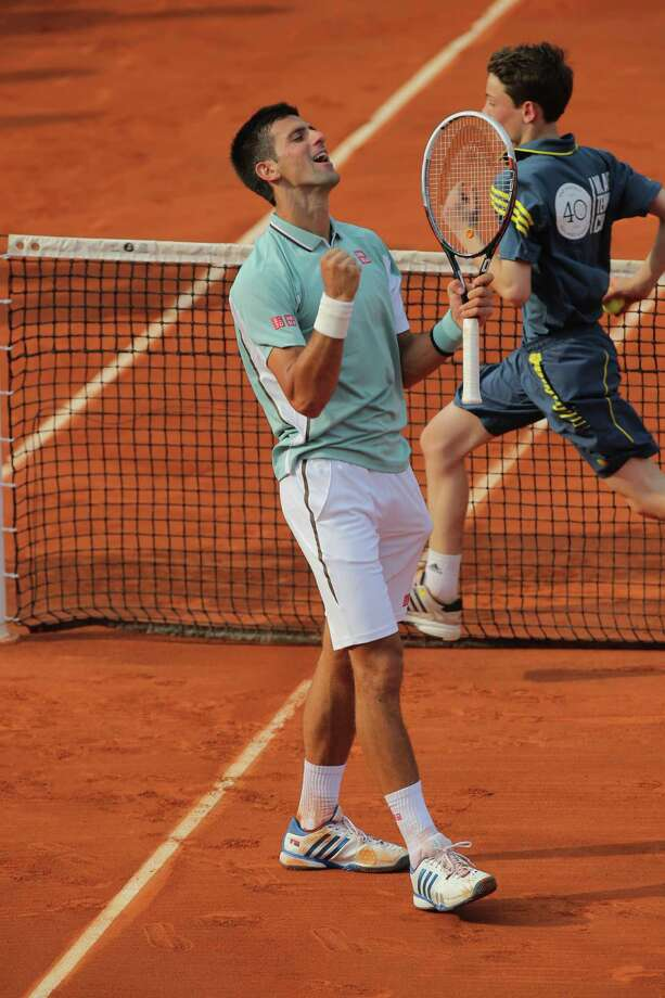 Serbia's Novak Djokovic celebrates defeating Germany's Tommy Haas in three sets 6-3, 7-6, 7-5, in their quarterfinal match at the French Open tennis tournament, at Roland Garros stadium in Paris, Wednesday June 5, 2013. (AP Photo/Michel Euler) Photo: Michel Euler