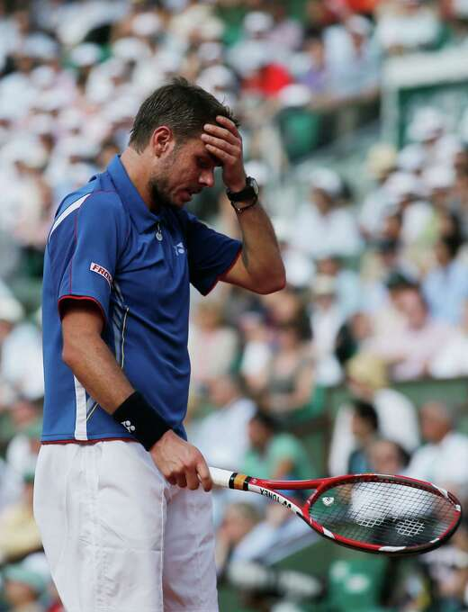 Switzerland's Stanisas Wawrinka holds his head as he plays Spain's Rafael Nadal during their quarterfinal match of the French Open tennis tournament at the Roland Garros stadium Wednesday, June 5, 2013 in Paris. (AP Photo/Christophe Ena) Photo: Christophe Ena