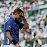 Switzerland's Stanisas Wawrinka holds his head as he plays Spain's Rafael Nadal during their quarterfinal match of the French Open tennis tournament at the Roland Garros stadium Wednesday, June 5, 2013 in Paris. (AP Photo/Christophe Ena)