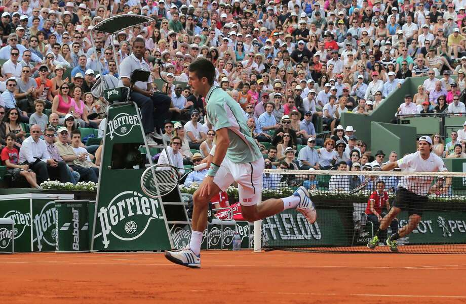 Serbia's Novak Djokovic runs to return the ball to Germany's Tommy Haas, right, during their quarterfinal match of the French Open tennis tournament at the Roland Garros stadium Wednesday, June 5, 2013 in Paris. (AP Photo/Michel Euler) Photo: Michel Euler