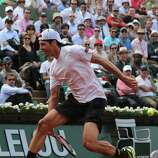 Germany's Tommy Haas makes an acrobatic return to Serbia's Novak Djokovic during their quarterfinal match of the French Open tennis tournament at the Roland Garros stadium Wednesday, June 5, 2013 in Paris. (AP Photo/Michel Euler)