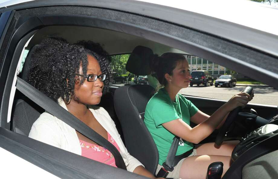 At left, Roselyne Opont, an instructor for All-Star Driver, a Norwalk driving school, gives a lesson to Norwalk resident, Cassidy Somma, 17, in the parking lot of the All Saints Catholic School in Norwalk, Wednesday, June 5, 2013. Photo: Bob Luckey / Greenwich Time