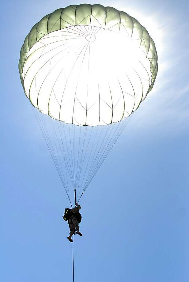 A paratrooper with the Army's 4th Brigade Combat Team (Airborne), 25th Infantry Division drops toward the Malamute Drop Zone on Joint Base Elmendorf-Richardson during a training exercise Wednesday, June 5, 2013 near Anchorage, Alaska. During the three-day exercise, the Army said more than 1,400 paratroopers and heavy equipment were dropped to simulate the takeover of hostile territory. (Matt Tunseth/Chugiak-Eagle River Star) Photo: Matt Tunseth, Associated Press