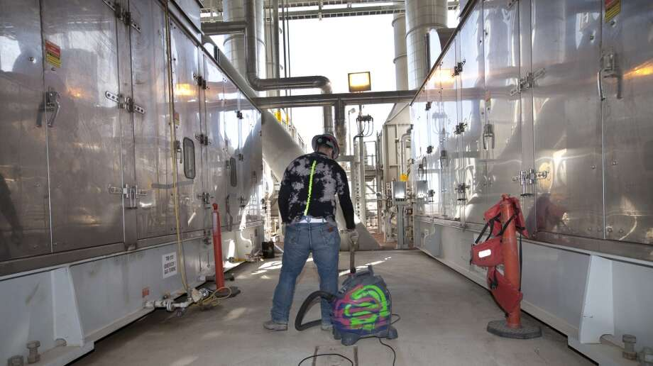 Shell is commited to nothing as small as chewing gum goes overboard into the work site at the Shell off-shore drilling platform Olympus at the Kiewit Off-Shore Services site at Ingleside, Texas Wednesday, June 5, 2013. A worker vacuums  the floor in the power module to keep even minor debris from being blown into the water at the work site. Photo: George Tuley, For The Houston Chronicle