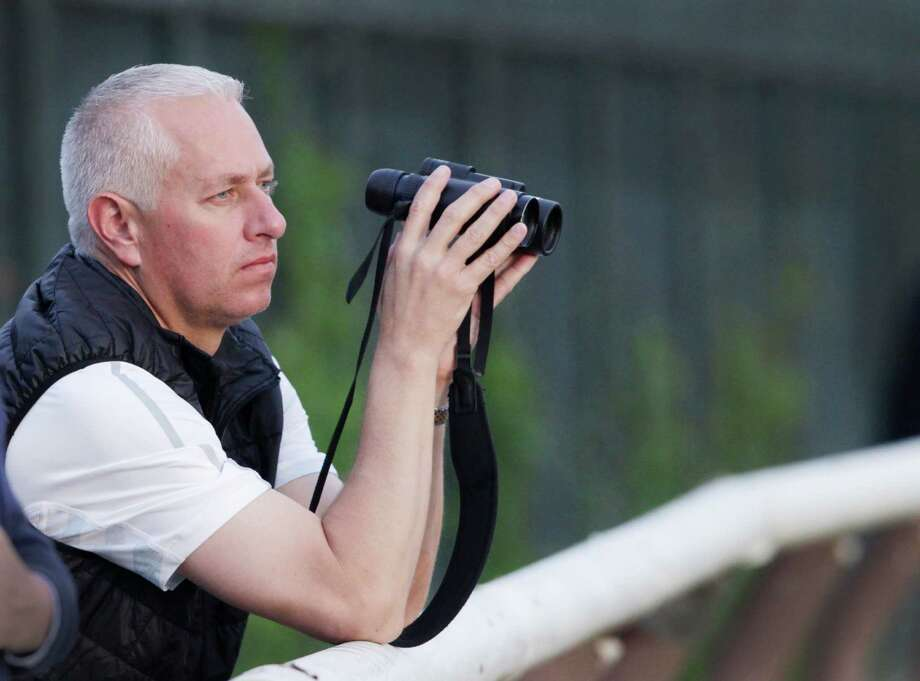 Trainer Todd Pletcher leans on the outside rail to watch his horses gallop on the track at Belmont Park during a morning workout Thursday, June 6, 2013 in Elmont, N.Y. Pletcher has five horses entered in Saturday's Belmont Stakes horse race. Photo: Mark Lennihan, AP / AP